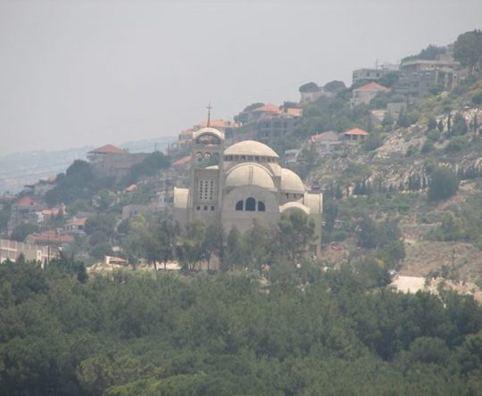 كاتدرائية القيامة في كفرعقا و تظهر في الخلفية بلدة كوسبا